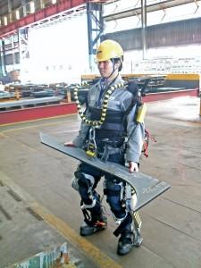 Ein Arbeiter trägt mittels Exoskelett ein schweres Metallteil, dass normalerweise nur mit einem Kran bewegt werden kann.